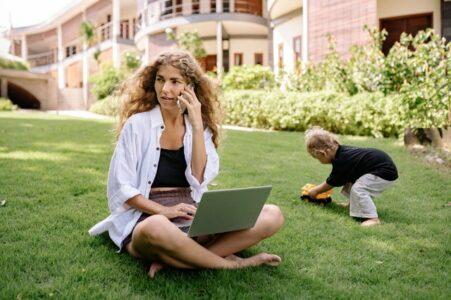 Une femme téléphone et utilise Woleet Sign sur son ordinateur dans un jardin